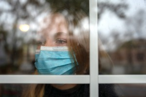 PRAIRIE VILLAGE, KS. - NOVEMBER, 10: Lilly Stecklein looks out the window of her home in Prairie Village, Ks. Tuesday November 10, 2020. Her family includes 10 people, three of whom have COVID-19. This means the whole family must quarantine indoors together and wear masks as well. States like Kansas have seen a steep increase in the number of COVID-19 cases.  (Photo by Christopher Smith/For The Washington Post via Getty Images)
